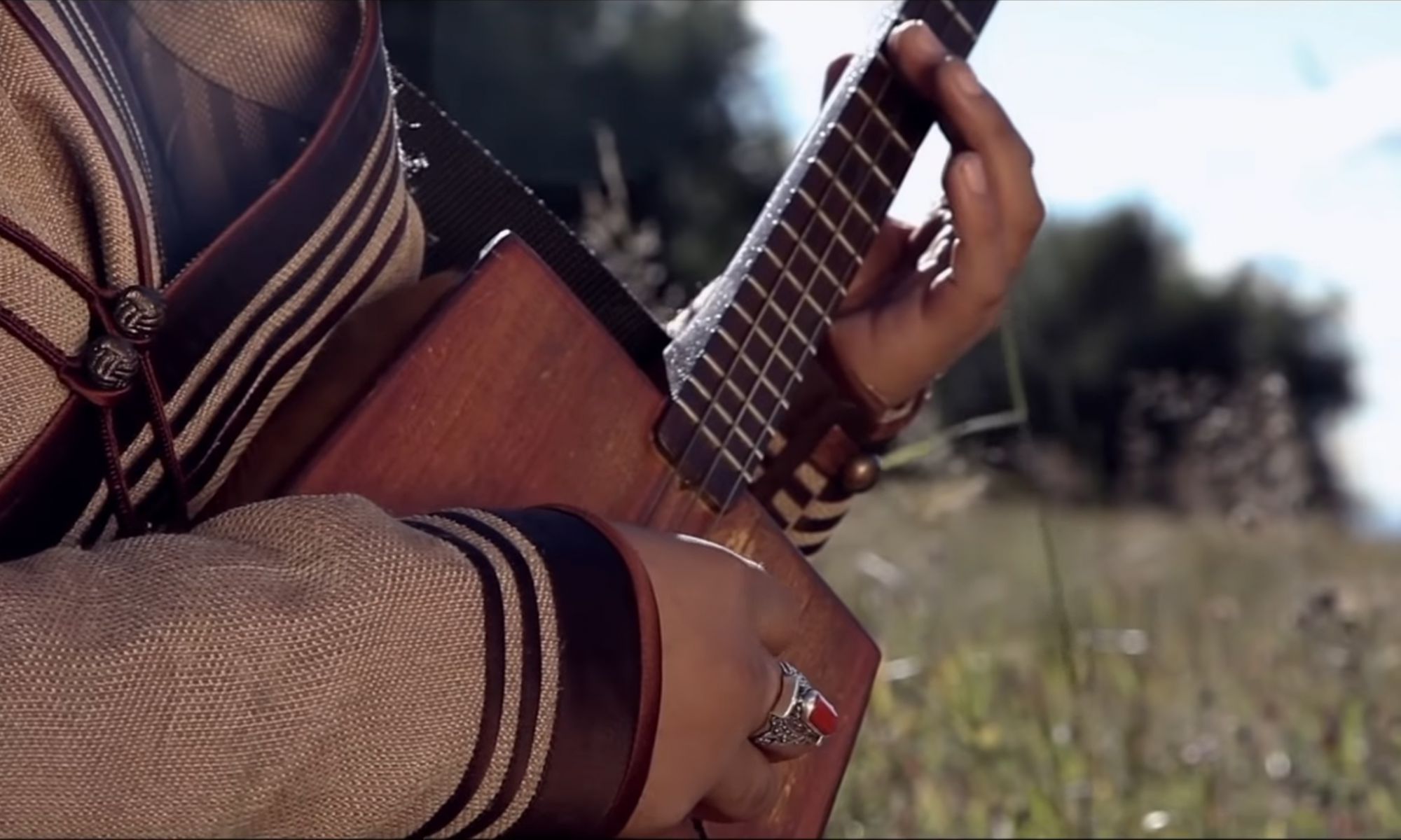 Closeup of someone playing a traditional 4 stringed guitar